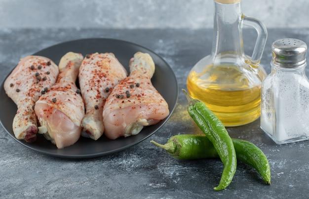 Сырая куриная голень со специями на сером фоне.
