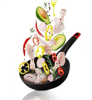 Сырые куриные ножки и овощи ингредиенты падают на сковороду.
