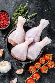 생 닭 나지만, 냄비에 허브와 향신료와 다리. 유기농 가금류. 검정색 배경. 평면도