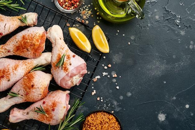 黒い石の背景に調理するための材料と生の鶏のドラムスティック。食品の背景、