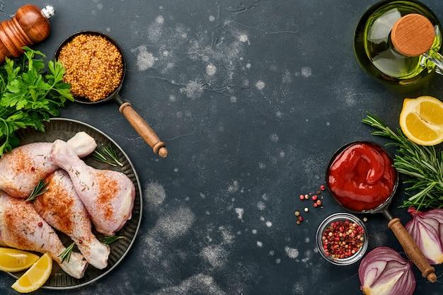 Сырые куриные голени с ингредиентами для приготовления на черной каменной поверхности. вид сверху.
