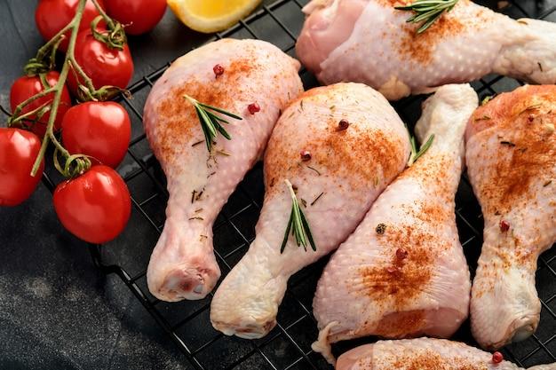 黒い石の表面で調理するための材料を使った生の鶏のドラムスティック