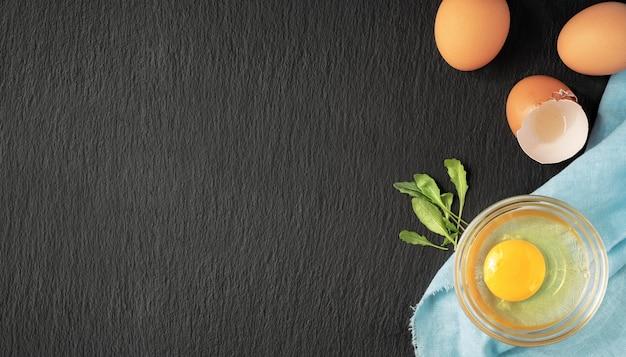 달걀 껍질 옆 유리 컵에 생 닭고기 달걀