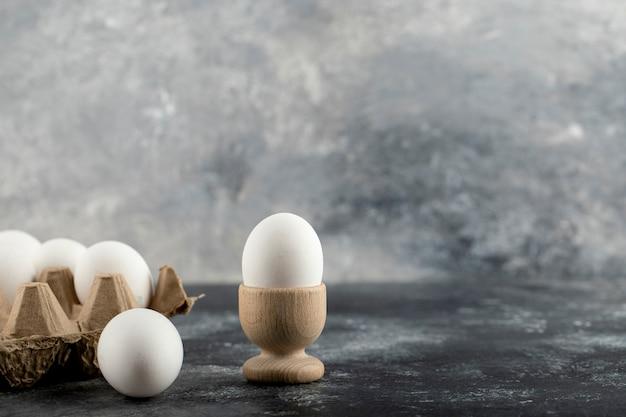 Сырое куриное яйцо в яичной чашке с ящиком для яиц на мраморной поверхности.