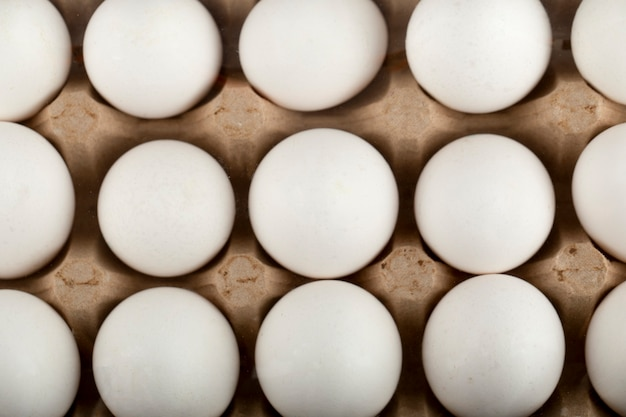 Raw chicken eggs in egg box on a marble surface.