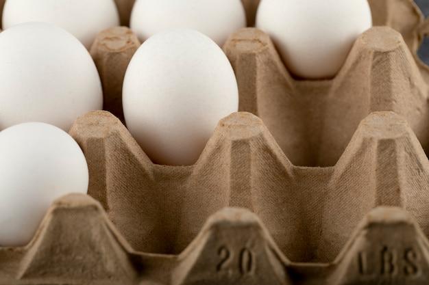 Uova di gallina crude in scatola per uova su una superficie di marmo.