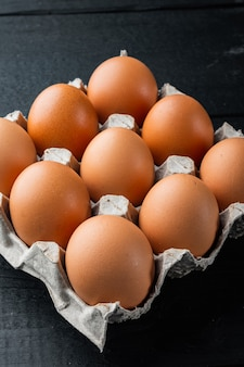 Raw chicken eggs in egg box set, on black wooden table background