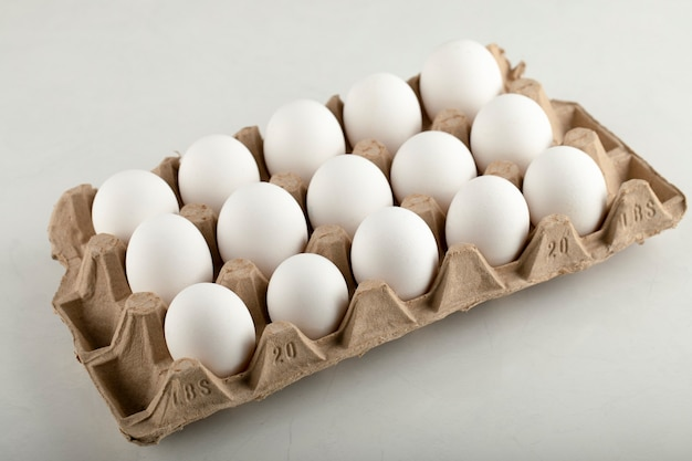 Raw chicken eggs in egg box on a white surface.