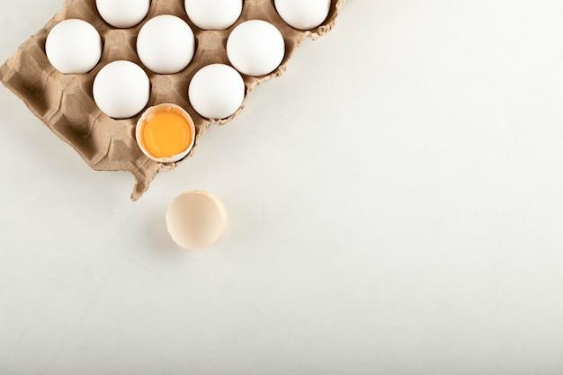 Uova di gallina crude in scatola per uova su una superficie bianca.
