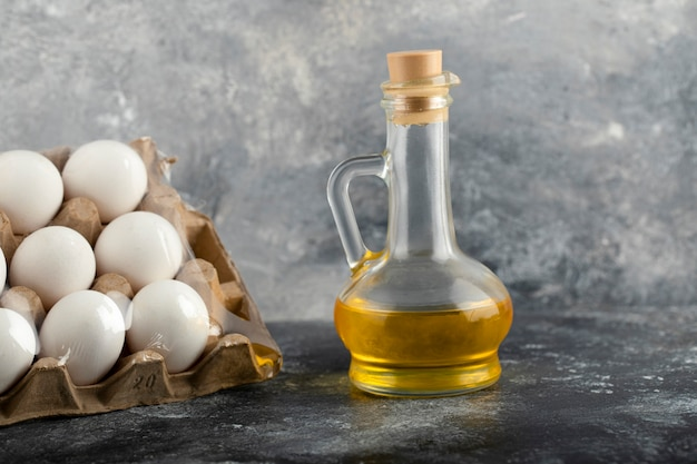 Raw chicken eggs in egg box with a glass bottle of oil.