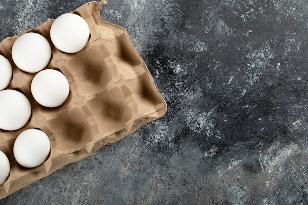Сырые куриные яйца в яичной коробке на мраморной поверхности.