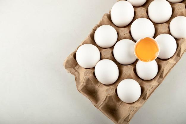 흰색 표면에 계란 상자에 원시 닭고기 달걀.