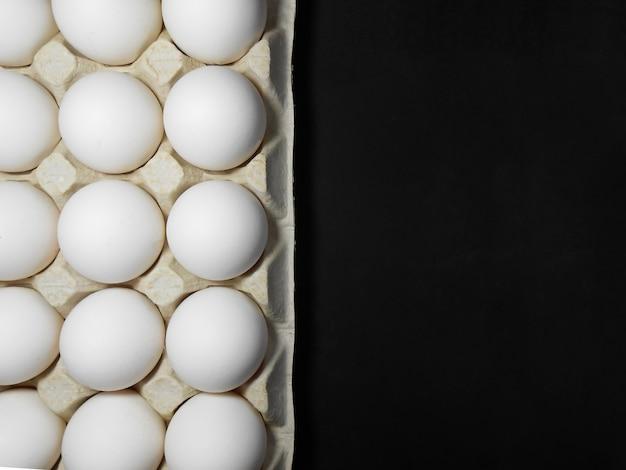Сырые куриные яйца в яичной коробке на черном фоне.