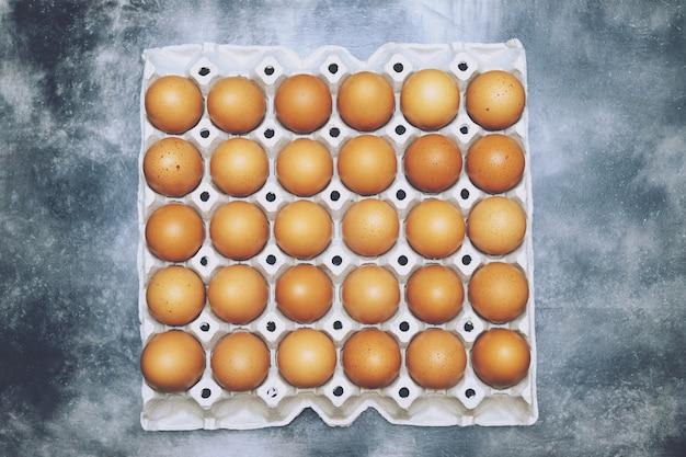木製のテーブルの上の卵ボックスに生の鶏の卵。