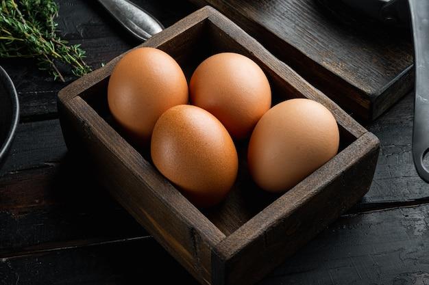 오래 된 어두운 나무 테이블 배경에 계란 상자 세트에 원시 닭고기 달걀