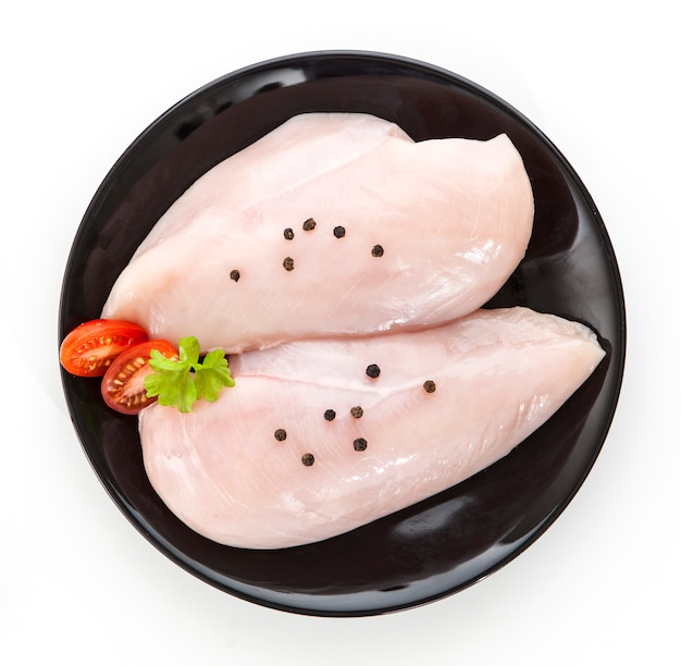 Raw chicken fillet on a black plate