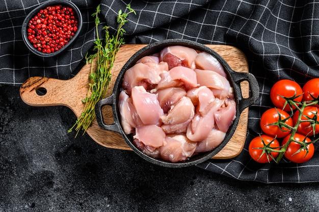 Сырое куриное филе нарезать кубиками со специями. черный фон. вид сверху
