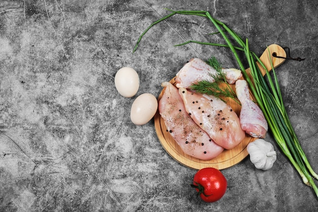 Raw chicken fillet and legs on wooden plate with fresh vegetables.
