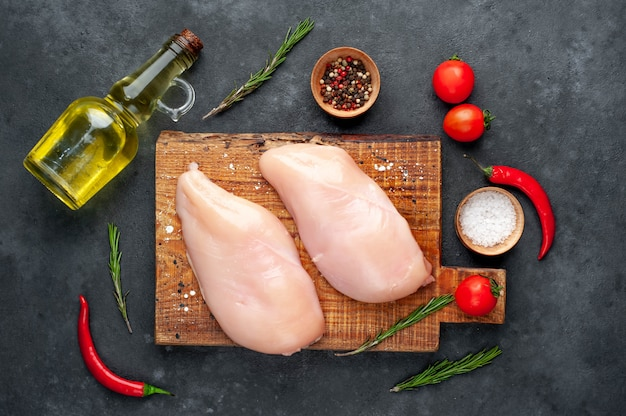 Raw chicken fillet , tomatoes and rosemary , sunflower oil on a stone background