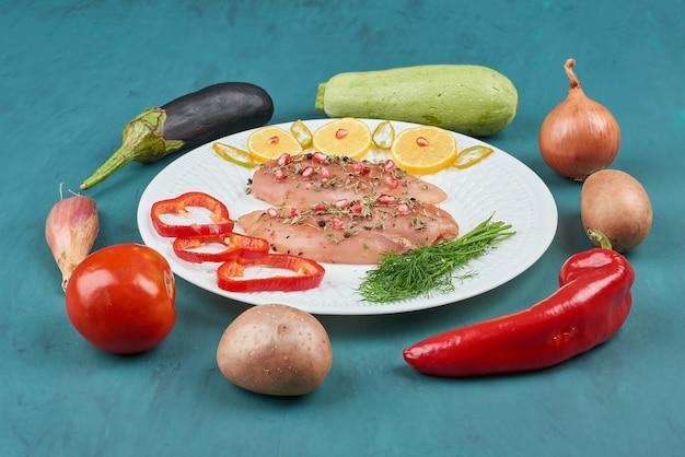 Filetto di pollo crudo in un piatto bianco con erbe e verdure.