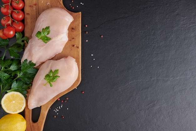 Сырое куриное филе с чесноком, перцем и розмарином на деревянной разделочной доске.