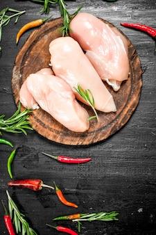 生の鶏肉の切り身とハーブとスパイス。黒い黒板に。