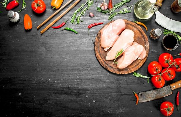 Сырое куриное филе с зеленью и специями. на черной поверхности.