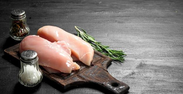 ローズマリーとスパイスを添えた生の鶏肉の切り身。