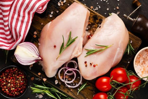 Сырое куриное филе со специями и зеленью на темной разделочной доске. готовим куриную грудку. приготовление пищи, диета здорового мяса. вид сверху.