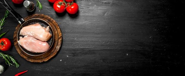 トマトとハーブを添えた生の鶏肉の切り身。黒い黒板に。