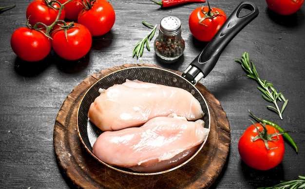 Сырое куриное филе с помидорами и зеленью на черной доске.
