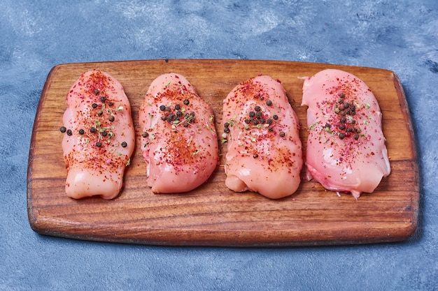 Raw chicken fillet on a wooden board on blue