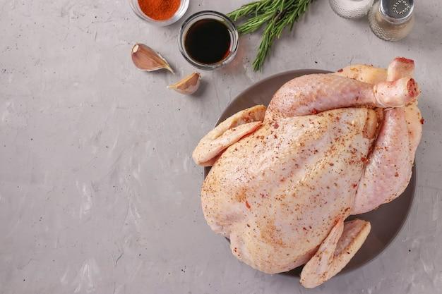 향신료로 기름을 바른 생닭 : 파프리카, 후추, 간장, 마늘, 회색 콘크리트 배경, 평면도, 텍스트를위한 공간