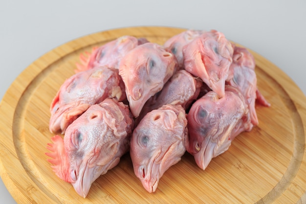 Сырые куриные головы на белом
