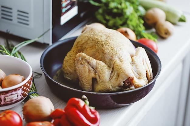 Сырая курица на кухне готова к приготовлению.
