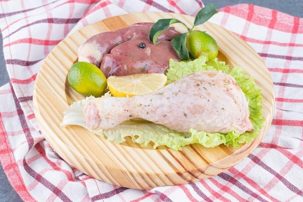 Сырые куриные ножки и говядина на деревянной тарелке.