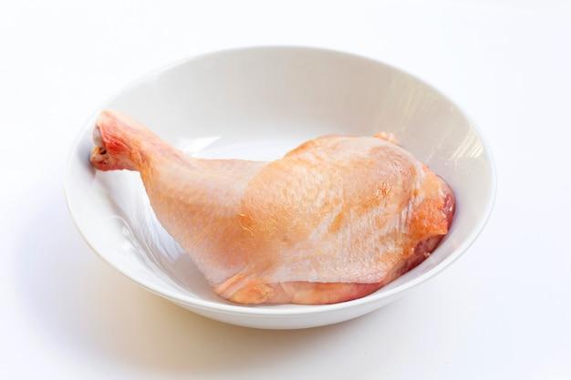 白い背景の上の白いボウルに生の鶏の脚