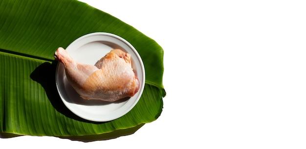 白い背景の上のバナナの葉に生の鶏の脚