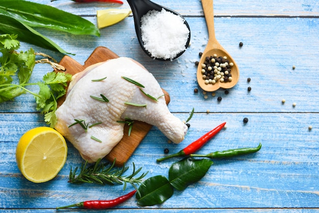 タイのアジア料理ローズマリーチキンレモンを調理するための木製の生の鶏の脚、上面図