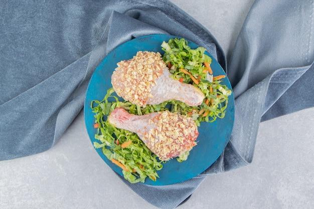 접시, 수건, 흰색 표면에 생 닭 다리 분기와 채소