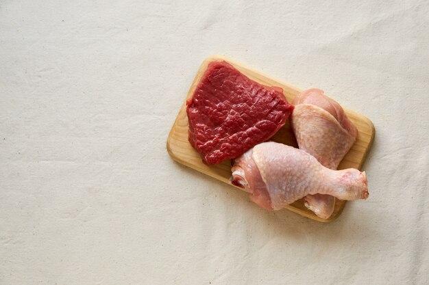 생 닭 다리와 나무 보드에 쇠고기 고기