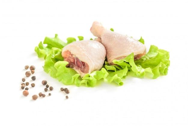 Сырые куриные ножки и зеленый салат, изолированные на белом фоне.