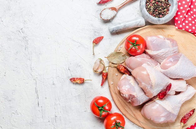Raw chicken legs on cutting board with spices and herbs.