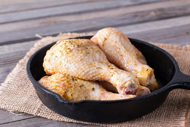 木製のテーブルのフライパンで生の鶏の脚