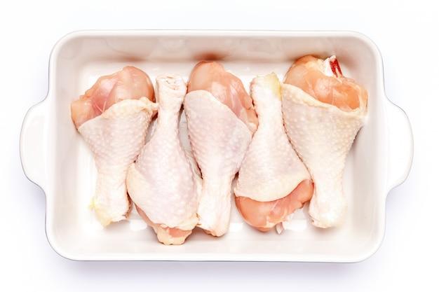 고립 된 흰색에 베이킹 접시에 생 닭 다리