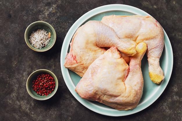 素朴な金属の背景の上にセラミックプレートで生の鶏の脚。ローフードのコンセプト。上面図。フラットレイ