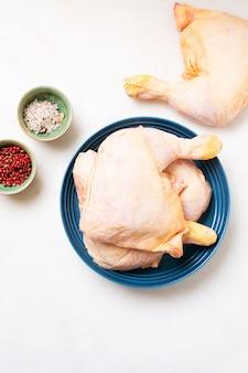 白い背景の上のセラミックプレートの生の鶏の足。ローフードのコンセプト。上面図。フラットレイ