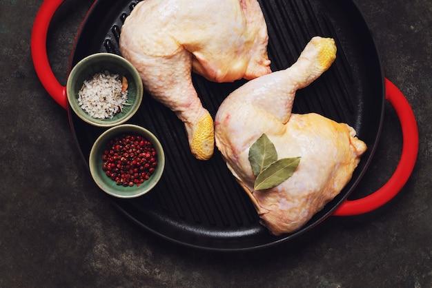 素朴な金属の背景の上に鋳鉄のグリル鍋で生の鶏の足。ローフードのコンセプト。上面図。フラットレイ