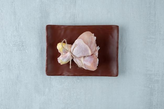 Cosce di pollo crude legate con corda sul piatto.