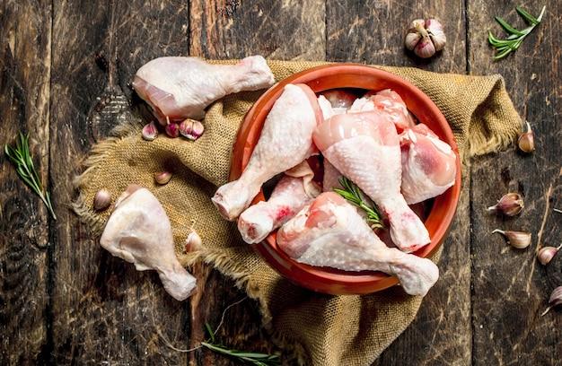 Сырые куриные окорочка с чесноком и специями в миске. на деревянном фоне.
